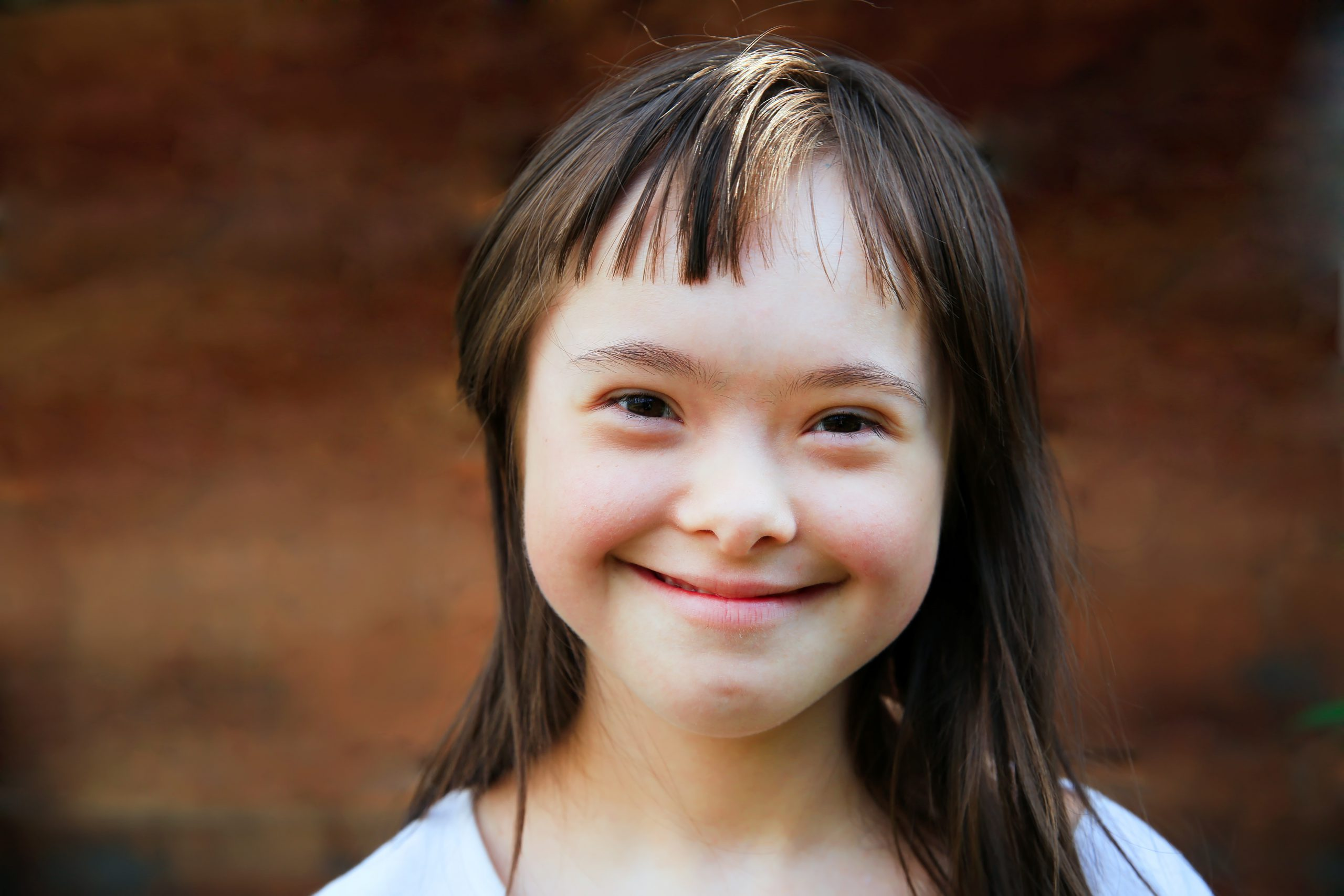 Cute smiling down syndrome girl on the brown background